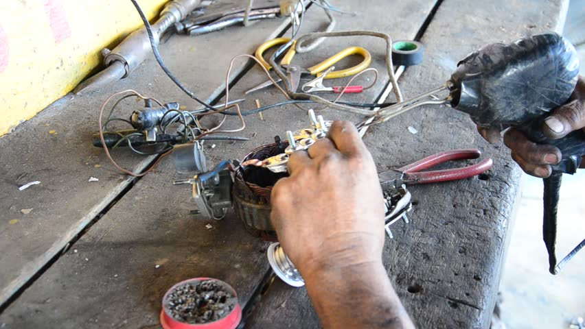Old man 60 year old thai people professional automotive motor mechanic lead-free solder for repair and inspecting the alternator of car at local shop in Nonthaburi, Thailand