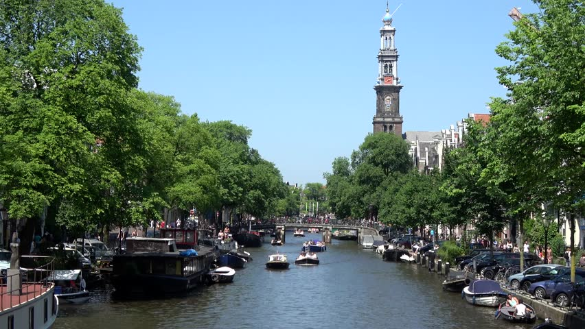 Amsterdam city center showing Westertoren church Westerkerk and typical Amsterdam canal Prinsengracht busy because of summer day blue sky background small boats moving over gracht tourist visit 4k
