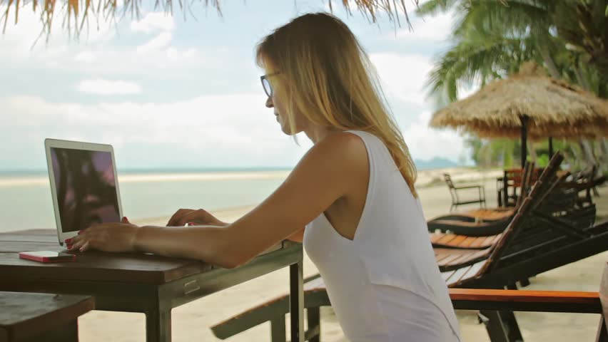 Young woman sitting at the table with a laptop in front of sea view. Lady freelancer working at the beach. | Shutterstock HD Video #17155345