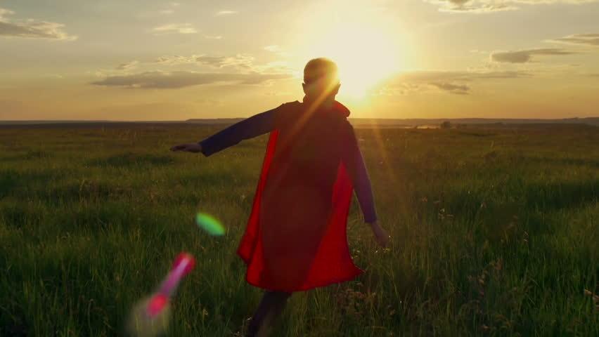 superhero boy running on the green field at sunset