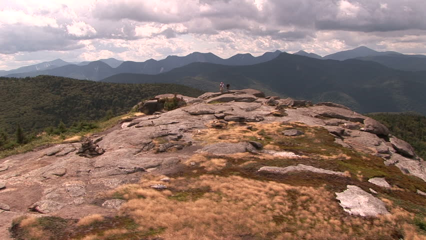 Family walks across summit towards camera