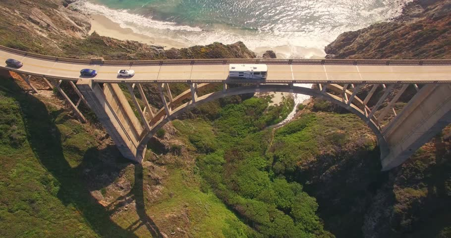 Aerial view RV, cars passing Bixby Creek Bridge on PCH Highway 1 with Pacific Ocean in background. Monterey, Big Sur, CA