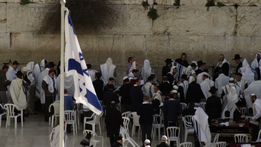 ISRAEL - FEB 2011: Israeli flag in the foreground and male Jews at the Western Wall (Wailing Wall)