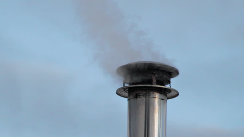 Smoke pouring out of a chimney cap on a metal stove pipe from a wood fire - Smoke Comes From The Chimney Of The House. The Pipe On The Roof