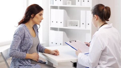 pregnancy, gynecology, medicine, health care and people concept - gynecologist doctor with clipboard and pregnant woman meeting at hospital