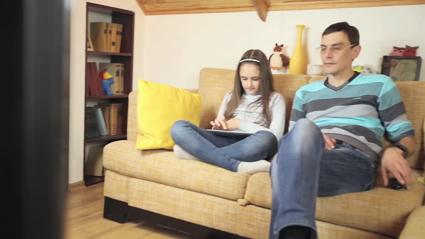 Father watching TV, playing the daughter of the tabletather and daughter playing games on a tablet. a happy family. | Shutterstock HD Video #17313298
