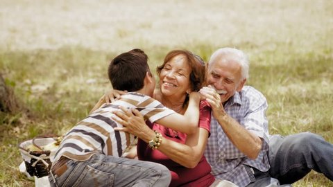 Old people, senior couple, elderly man and woman, husband and wife in park. Outdoors activity, leisure, family recreation. Happy grandfather and grandmother hug grandson, boy, child. Slow motion
