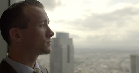 Handsome young business man looks across Los Angeles from Downtown office window.  Big close up with sunrise sky, dolly shot originally recorded in 4K