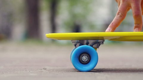 Finger skateboarding concept. Fingers riding big blue and yellow skate board. Youth having outdoor fun with finger skateboarding. Skateboard joke on asphalt in urban space.