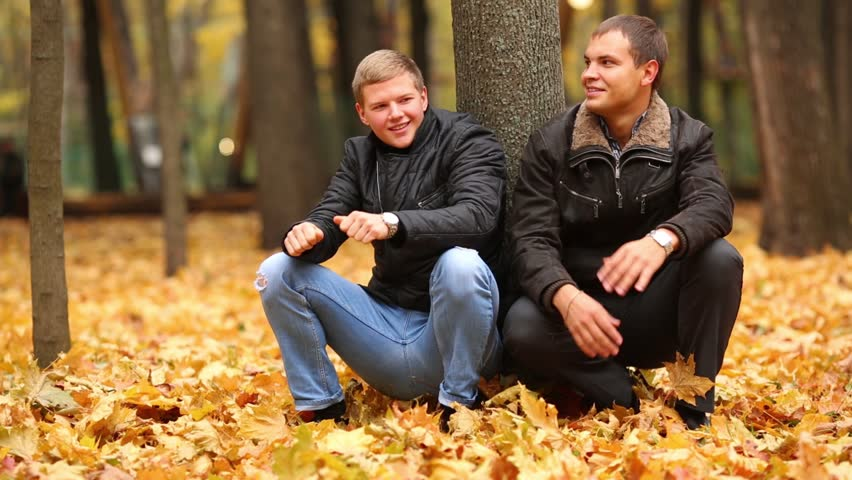 Two men sit on their haunches beside a tree in autumn park and talking
