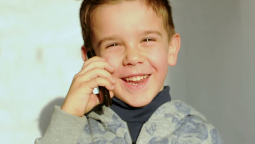 Child speaks on the phone and laughs
