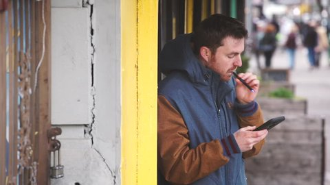 A man smokes an e-cigarette while talking on the phone. New York - April 1, 2016