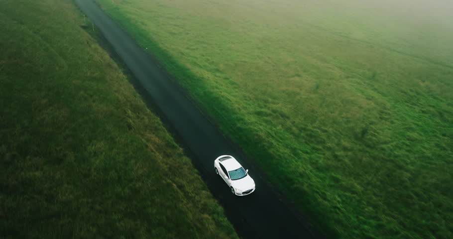 Aerial view electric car driving on country road, luxury car driving through mist at dusk with headlights | Shutterstock HD Video #17360539