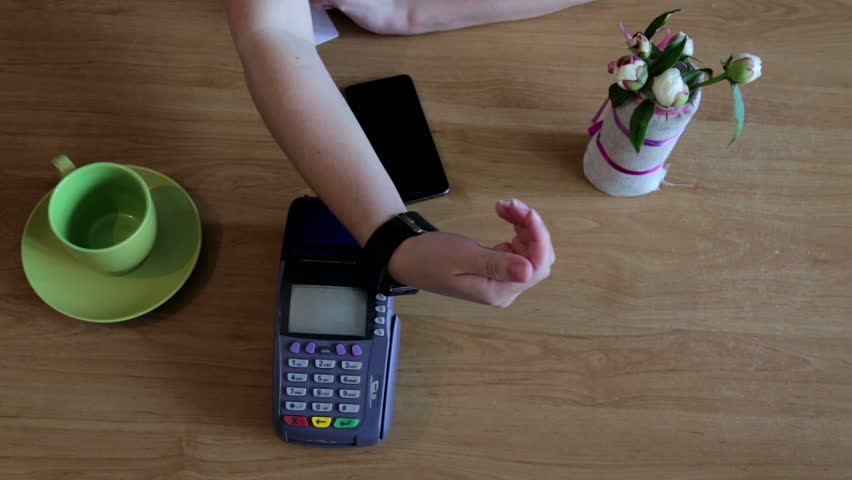 Girl was paying using a smart watch in a cafe