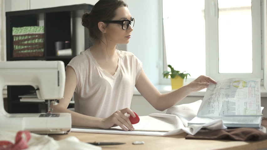 Focused Attractive Young Woman Tailor Sitting And Drawing On White Textile  Material   4K Stock Footage