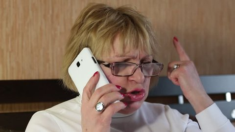 Angry woman communicates via smartphone. Blonde woman with white smartphone. Female talks on the cell phone. Woman with smartphone communicates through smartphone. Businesswoman with mobile phone