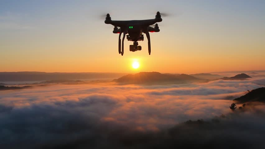 Drone flying over cloud in morning, in a aerial shot,  drone moving in to the sun.