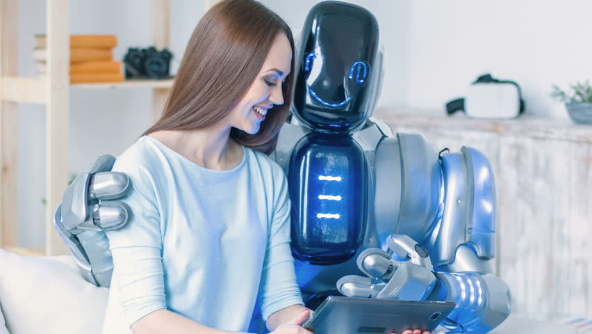 Positive woman sitting on the couch with modern robot