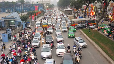 A crowded mess of motorbikes, cars and buses during rush hour at a big street in Hanoi, capitol of Vietnam. Wide shot.