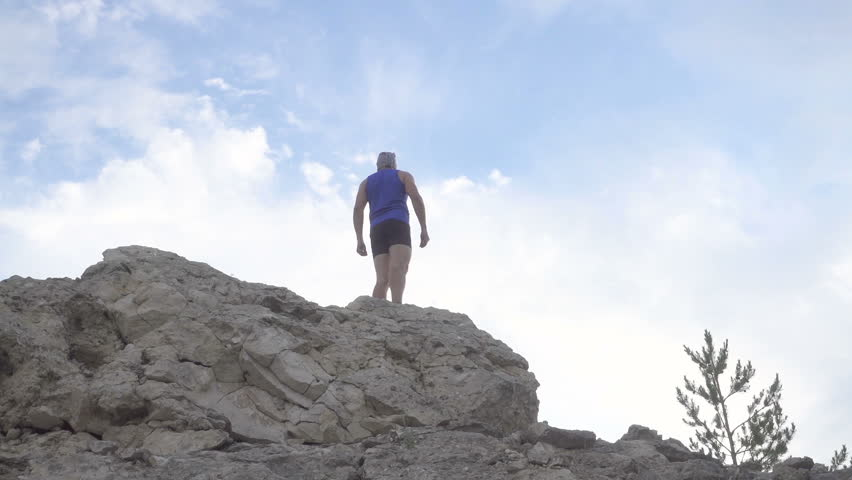 Slow motion. Man climbs on top of the mountain. Running over rough terrain. | Shutterstock HD Video #17459077