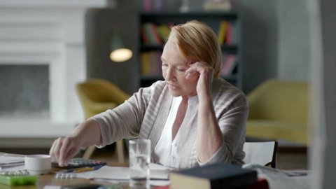 Unhappy troubled elderly woman incredulously looks at a pill. don't want to take medical drugs
