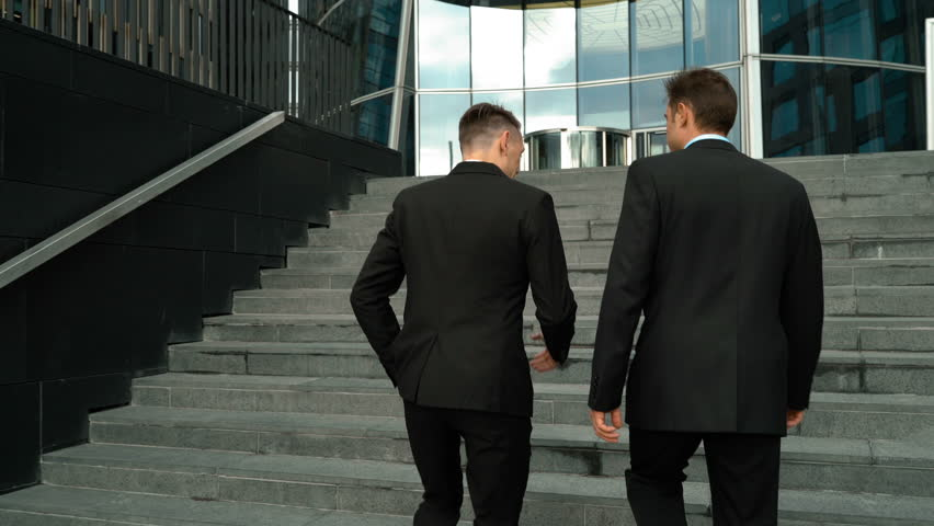 Two young friendly businessmen communicating with carefree morning conversation. They by climbing the stairs. Glossy business-centre building at the background. Teal-and-Orange style. Middle 4k