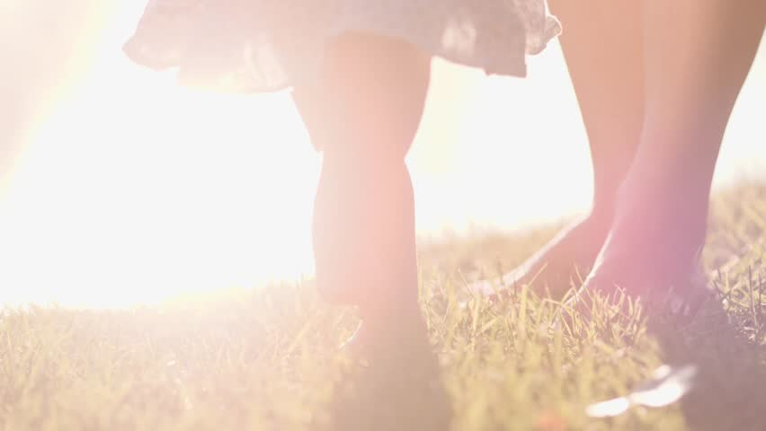Little baby learns to walk. First Steps. Slow Motion 120 fps, 4K. Mother is teaching her child to do the first steps on a green grass in summer. Close up on feet. Happy childhood and Maternity. Family | Shutterstock HD Video #17520448