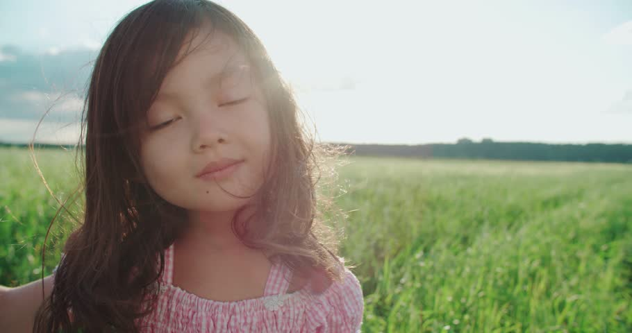 little Asian girl standing in a green field of young wheat,close-up, flowing hair,slow motion,sunset