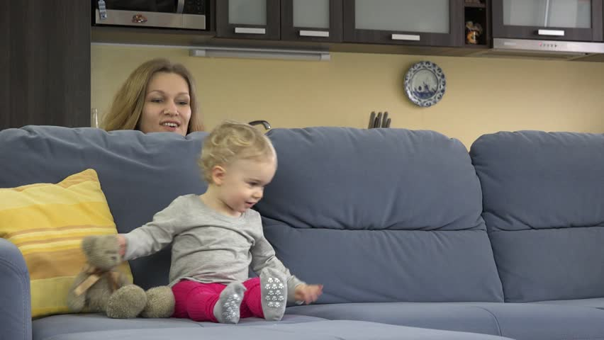 Young Mother Play Hide And Seek Under Sofa With Her Cute Toddler Daughter.    4K