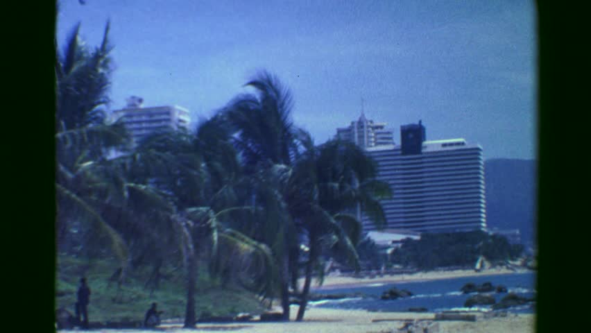 ACAPULCO, MEXICO 1978: Skyscraper resort beach hotels parasailing tropical paradise tourism.