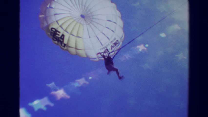 ACAPULCO, MEXICO 1978: Parasailing man parachute landing on beach helped by staff.