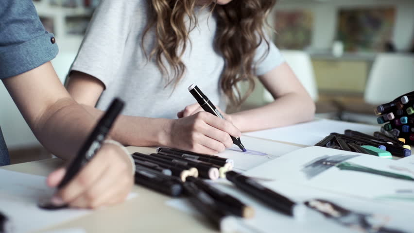 Designers draw sketches in the Studio. two attractive women working and smiling. Workspace designer. White sheet of paper, pencils, markers, felt-tip pens. | Shutterstock HD Video #17609293