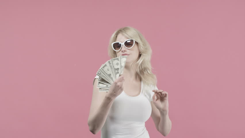 Blonde woman throws american dollars in the air and celebrates against pink background