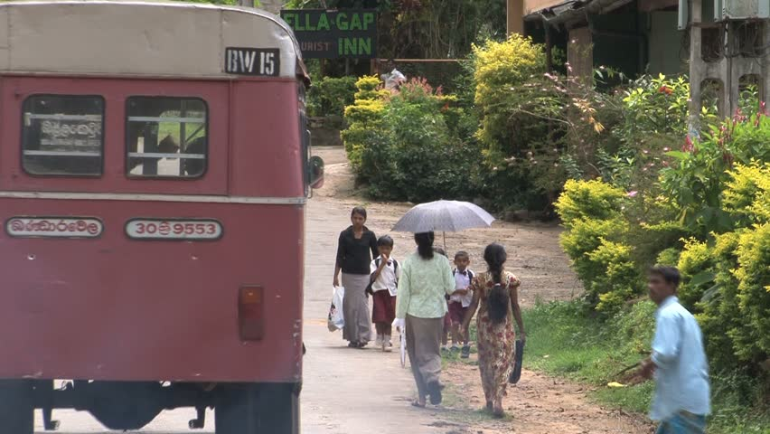 ELLA, SRI LANKA - CIRCA APRIL 2011: People and automobiles travel down a commercial street