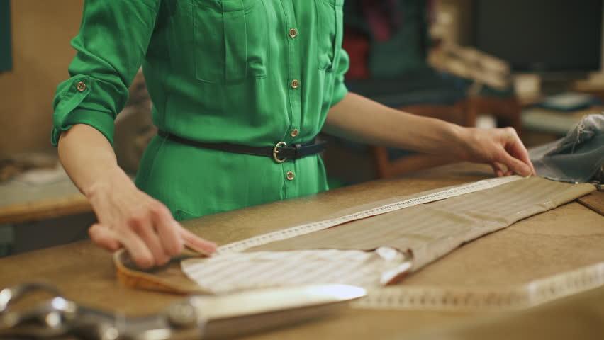 Young Woman Fashion Designer Works in Studio. Using Measuring Tape. Shot in 4K (UHD).