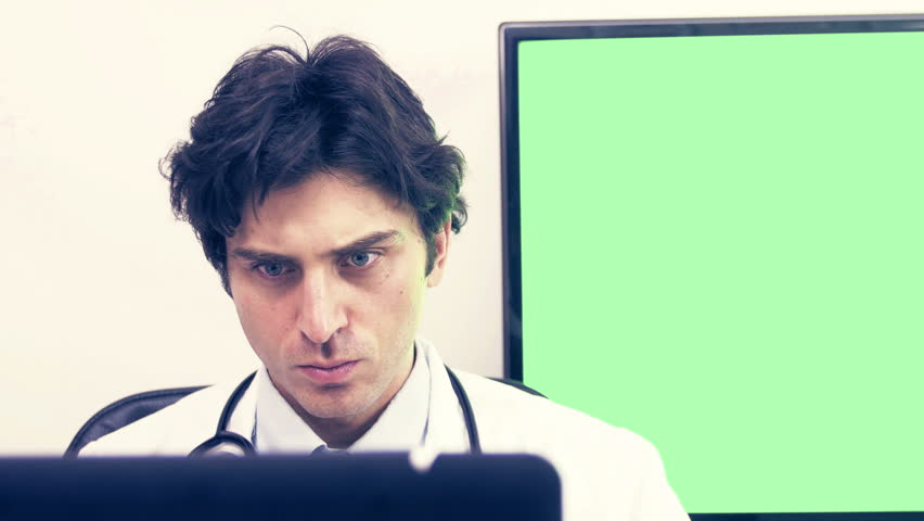 Portrait Of Tired Doctor Working On Computer In Medical Office ...