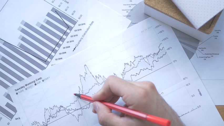 Analyzing some stock market reports and taking notes over them. | Shutterstock HD Video #17663017