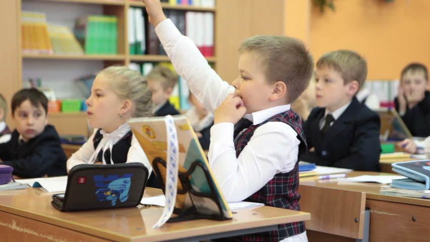 ST. PETERSBURG, RUSSIA - CIRCA MAY, 2016: Young schoolboy wants to answer the question and lifts the hand. Lesson is in Russian elementary school | Shutterstock HD Video #17670508