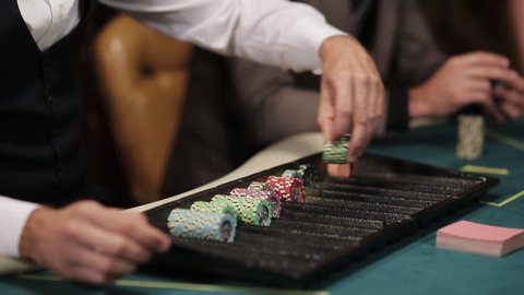 The dealer at the poker table lays chips under par. the game of poker. A croupier in a casino at a poker table arranges the chips according to the value. Close-up of hands of the dealer.