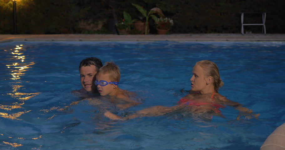 Pas Teaching Their Son To Swim In The Pool Young Family