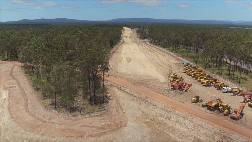 AERIAL: Flying close above big and dusty heavy industry construction site zone. Building, constructing and widening multilane highway road surrounded by stunning wild vast green lush forest   Shutterstock HD Video #17735668