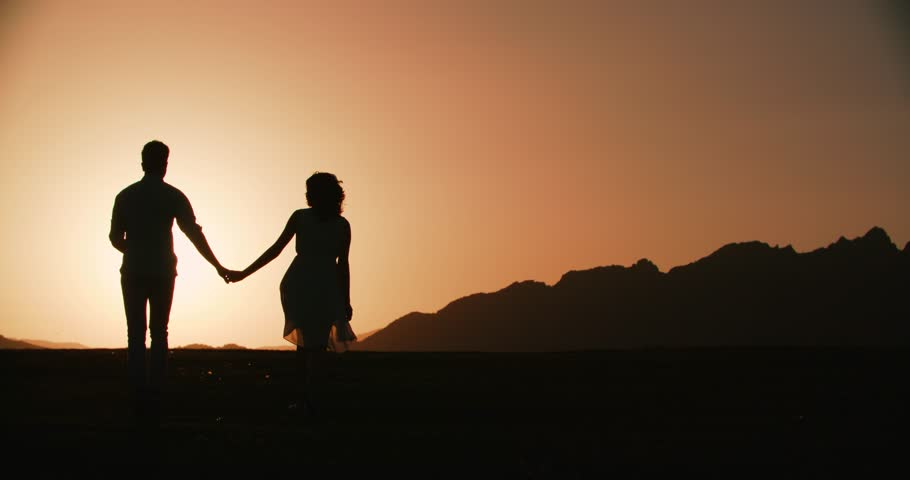 couple silhouette running forward holding hands with the sunset golden hour the sun a warm
