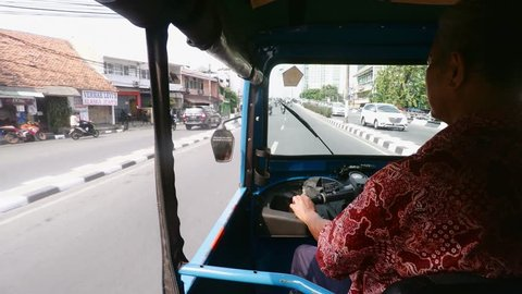 JAKARTA - August 10: Tuk Tuk motorized rickshaw common form of public transport in South East Asia, on August 10, 2015 in Jakarta, Indonesia. View from vehicle to street.