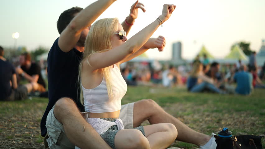 4k footage, happy young couple sitting on meadow at summer open air concert enjoying good music during late afternoon