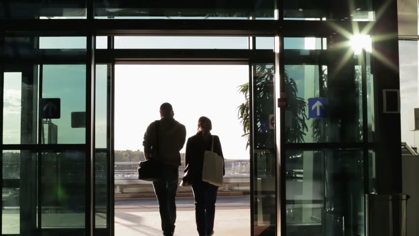 Man and woman come in the sliding door of the airport a guy with a the guy and the girl out of the door of the airport bright sun reflected planetlyrics Choice Image
