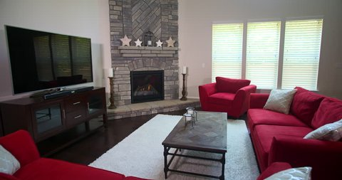 Modern Living Room Revealed from Behind Sofa. camera rises from behind a couch to reveal a modern furnished living room with red furniture, a fireplace, and entertainment console