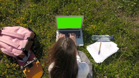 Top View of a Student Using Laptop With Green Screen While Lying On The Grass