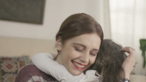 4K Daughter rushes into mother's arms at home and gives her a big hug. Shot on RED EPIC Cinema Camera in slow motion.