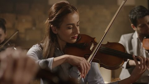 4K Close-up of musician playing violin on the symphony hall. Shot on RED EPIC Cinema Camera in slow motion.