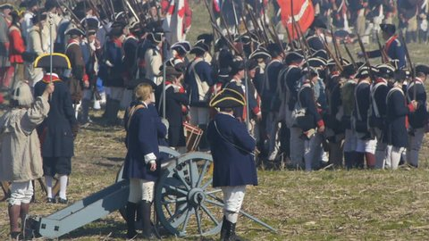 VIRGINIA - OCTOBER 2014 - Reenactment, large-scale, epic American Revolutionary War anniversary recreation -- in the middle of battle.  Cannons fire with British Redcoats and Continental Soldiers.